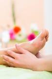 Femme dans le salon de clou recevant le massage de pied Photographie stock