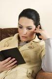 Femme dans le sofa affichant un livre Photos stock