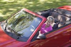 Femme dans le sourire convertible de véhicule photo stock