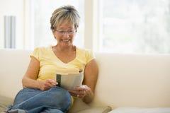 Femme dans le sourire de livre de relevé de salle de séjour Photo stock