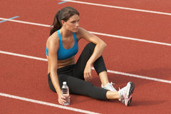 Femme dans le soutien-gorge de sports avec la bouteille d'eau sur la détente de piste Photo libre de droits