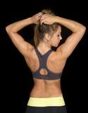 Femme dans le soutien-gorge de sports de noir des mains arrières de regard dans les cheveux photos stock