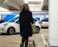Femme dans le stationnement marchant à la voiture pussing de supermarché de voitures images libres de droits