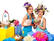Femme dans le style de Pâques tenant des oeufs et des fleurs Images stock