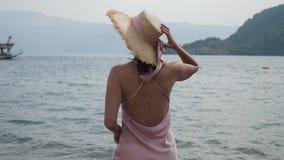 Femme dans le support en soie rose de robe et de chapeau de paille sur la plage banque de vidéos