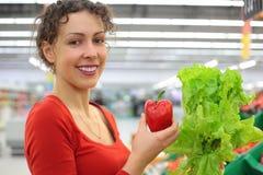 Femme dans le système avec le paprika et la salade Photo stock