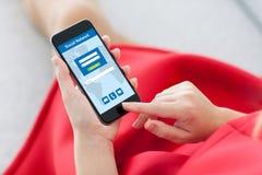 Femme dans le téléphone rouge de participation avec le réseau social sur l'écran Images stock