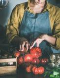 Femme dans le tablier de toile prenant des tomates hors du panier image stock