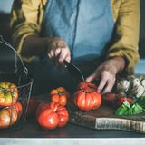 Femme dans le tablier faisant cuire la sauce tomate ou les pâtes, culture carrée photographie stock libre de droits