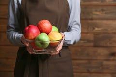 Femme dans le tablier tenant le bol en verre avec les pommes juteuses, Image stock