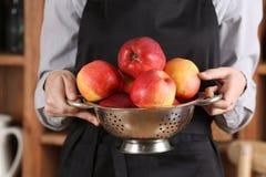 Femme dans le tablier tenant la passoire avec les pommes juteuses, Photos stock