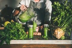 Femme dans le tablier versant le smoothie vert du mélangeur pour mettre en bouteille images stock