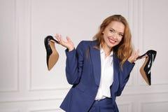 Femme dans le tenue de soirée se tenant dans des chaussures de chaque main image libre de droits