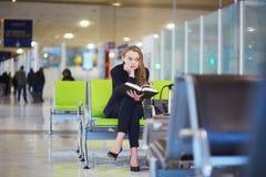 Femme dans le terminal d'aéroport international, livre de lecture Photos libres de droits