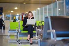 Femme dans le terminal d'aéroport international, travaillant sur son ordinateur portable Photographie stock libre de droits