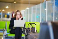 Femme dans le terminal d'aéroport international, travaillant sur son ordinateur portable Images libres de droits