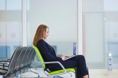Femme dans le terminal d'aéroport international, travaillant sur son ordinateur portable Image libre de droits