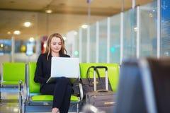 Femme dans le terminal d'aéroport international, travaillant sur son ordinateur portable Photo libre de droits