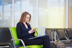 Femme dans le terminal d'aéroport international, vérifiant son téléphone Photographie stock libre de droits