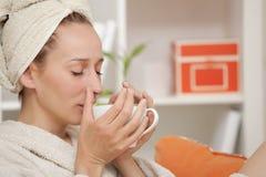 Femme dans le thé potable de peignoir images stock