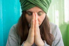 Femme dans le turban avec les yeux fermés tenant des mains dans le signe de Namaste Images libres de droits