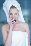 Femme dans le verre à boire de serviette de Bath de vin rouge Images stock