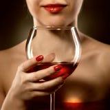 Femme dans le verre et les sourires de vin se tenant rouge image stock