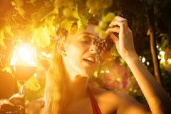 Femme dans le vignoble avec la vigne et les raisins Photo stock