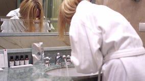 Femme dans le visage de lavage de peignoir blanc dans la vue de dos de pièce d'évier de salle de bains banque de vidéos