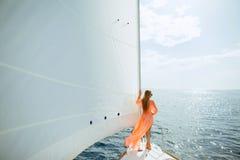 Femme dans le voyage de luxe de plaisance de voiles blanches de sarongs