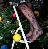 Femme dans les bas décorant l'arbre de Noël Photos stock