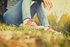 Femme dans les blues-jean et des espadrilles rouges de toile se reposant dans une herbe Photo libre de droits