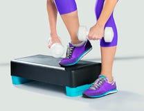 Femme dans les espadrilles et les vêtements de sport violets avec des haltères sur l'aerobi Photos stock