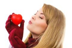 Femme dans les gants de laine tenant le coeur rouge et envoyant le baiser, symbole de l'amour Photographie stock