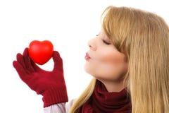 Femme dans les gants de laine tenant le coeur rouge et envoyant le baiser, symbole de l'amour Image stock