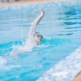Femme dans les lunettes nageant le style de rampement avant Photos libres de droits