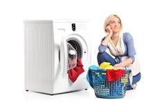 Femme dans les pensées posées à côté d'une machine à laver Photographie stock libre de droits
