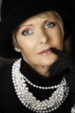 Femme dans les perles et le chapeau Photographie stock libre de droits