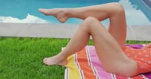 Femme dans les vêtements de bain détendant près du poolside dans l'arrière-cour 4k clips vidéos