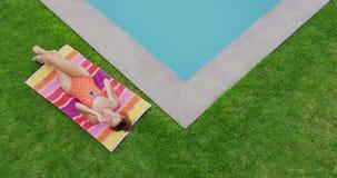 Femme dans les vêtements de bain détendant près du poolside dans l'arrière-cour 4k banque de vidéos
