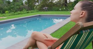 Femme dans les vêtements de bain détendant sur la chaise près de la piscine dans l'arrière-cour 4k banque de vidéos