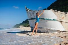 Femme dans les vêtements de bain marchant sur la plage sablonneuse pendant le bateau cassé proche de jour Photographie stock