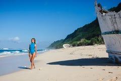 Femme dans les vêtements de bain marchant sur la plage sablonneuse pendant le bateau cassé proche de jour Photo stock