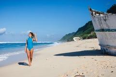 Femme dans les vêtements de bain marchant sur la plage sablonneuse pendant le bateau cassé proche de jour Photographie stock libre de droits