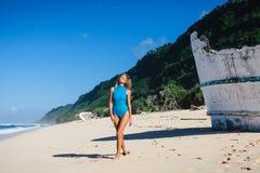 Femme dans les vêtements de bain marchant sur la plage sablonneuse pendant le bateau cassé proche de jour Images stock