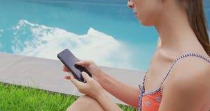 Femme dans les vêtements de bain utilisant le téléphone portable dans l'arrière-cour 4k banque de vidéos