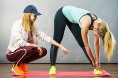 Femme dans les vêtements de sport faisant la séance d'entraînement avec l'entraîneur Images stock