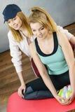 Femme dans les vêtements de sport faisant la séance d'entraînement avec l'entraîneur Photographie stock