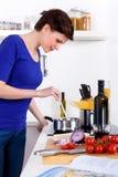 Femme dans sa cuisine préparant un plat de pâtes Photos libres de droits