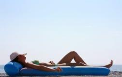 Femme dans un bikini vert se trouvant sur la plage photographie stock libre de droits